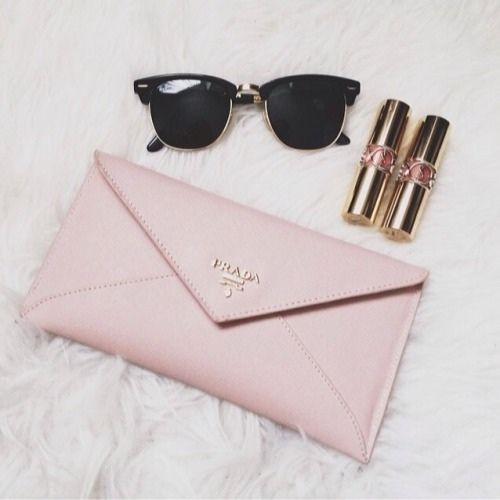 Pink Prada envelope wallet purse with YSL lipstick and Raybans