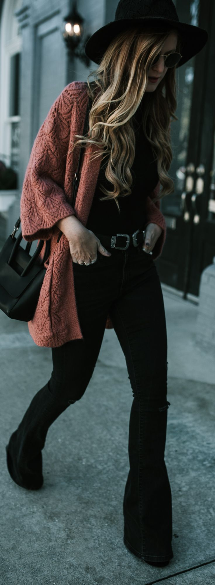 Boho winter outfit styled with coral cozy cardigan, black flared jeans, and doub…