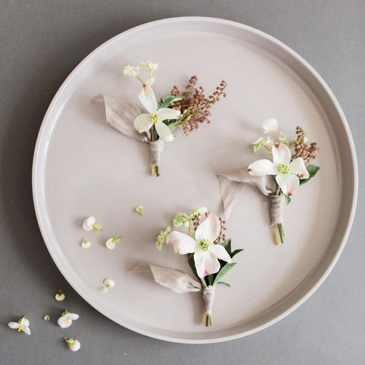 Simple boutonnieres by Studio Mondine on a handmade ceramic plate.
