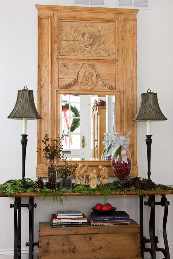 Greenery, pinecones, wooden nativity figures, and a vase filled with cranberries greet guests immediately inside this home. - Traditional Home ® / Photo: Gordon Beall / Design: Barbara Svihla and Olivia Paxton