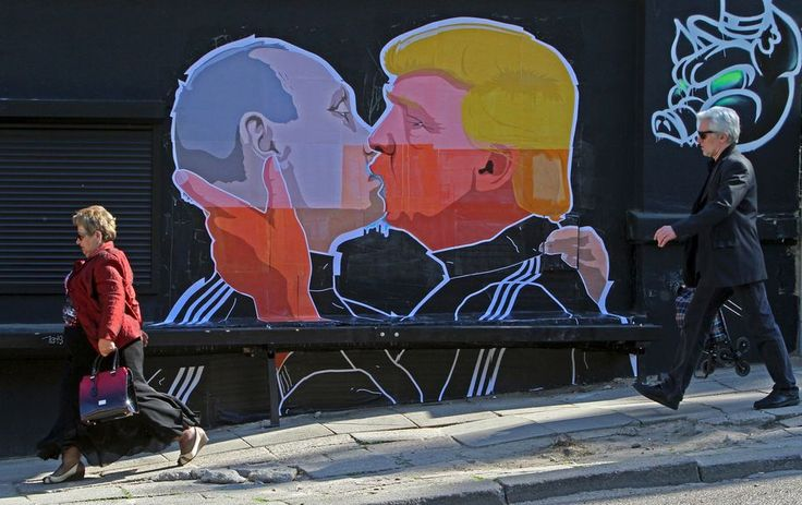 TOPSHOT - People walk past a mural on a restaurant wall depicting US  Presidential hopeful Donald Trump and Russian President Vladimir…