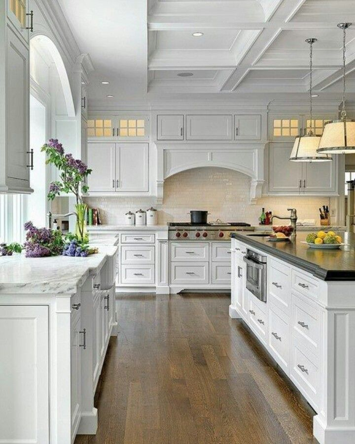 White kitchen. Love the top cupboard lighting and the microwave in the island