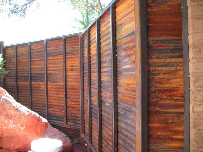 LOOKS LIKE wood but its a purposely rust sheet metal fence...maybe I could use this to hide that 'wide' area behind the house that the coyotes come out of.