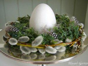 schaal met krans met wilgentak( katjes ) mos en veren en in het midden een ei.