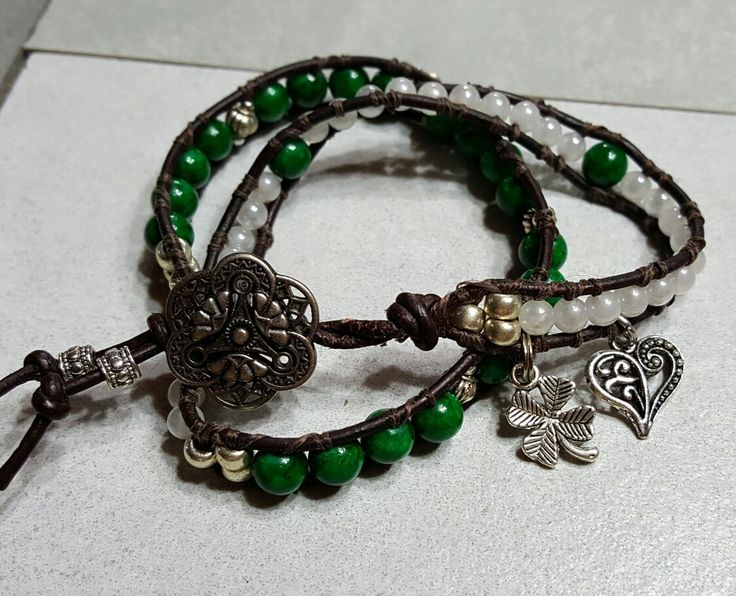 Go Irish with this double wrap bracelet. Features green Mountain Jade and white glass pearls framed by black leather. Floral open cut button closure. Accented with a silver tone lucky 4 leaf clover and a filigree heart charms.