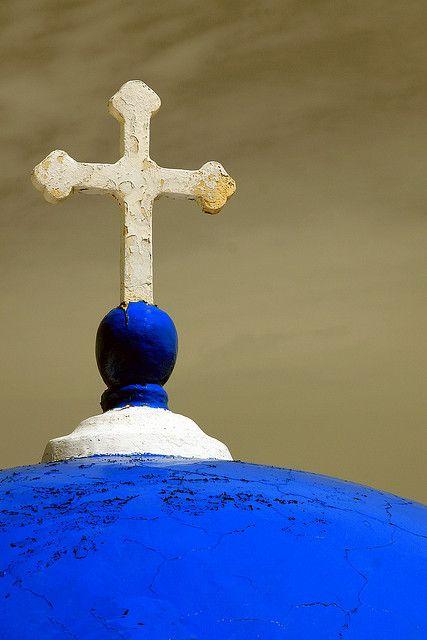 White cross and blue dome in Santorini island Cyclades Aegean Greece