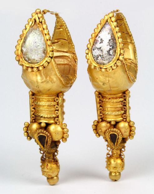 Roman Gold Earrings, c. 3rd Century BC The hollow crescent bodies of this pair of large Eastern Roman boat-shaped earrings terminate in wire hoops and are decorated on the front with applied drop-shaped box settings inlaid using glass.  Attached below the earrings is a cluster of ornate sprees and smaller drop-shaped compartments bearing pieces of polished carnelian that echo the larger glass setting above.
