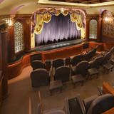 Similarto its entrance, the theater boasts a classic purple and gold color paired with cherrywood panels andcolumns. The theater seats are designed to mirror 1920s style and can seat 20 people.