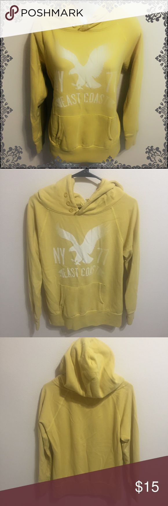 """Yellow American Eagle Hoodie American Eagle Outfitters. Size medium. Yellow hooded sweatshirt. Has three buttons at the neck and a pocket at the front. Faded white print on the front. In great condition, only defect is a small faded line stain located on the back beneath the hood (hardly noticeable; see picture). Made of 60% cotton, 40% polyester.   Measurements (approximate): Length (excluding hood): 26"""" Pit to pit: 20"""" Collar to sleeve cuff: 25"""" American Eagle Outfitters Tops Sweatshirts…"""