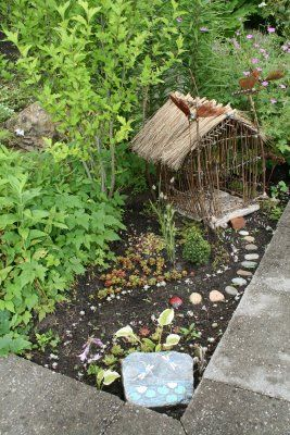 fairy garden. love the little stone pathway, and the twig cabin