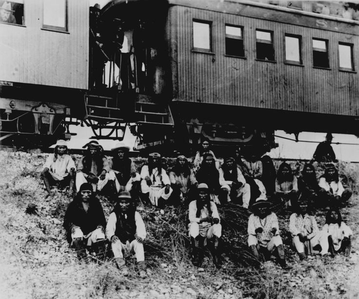 Band of Apache Indian prisoners at rest stop beside Southern Pacific Railway, near Nueces River, Tex., September 10, 1886. Among those on their way to exile in Florida are Natchez (center front) and, to the right, Geronimo and his son in matching shirts.