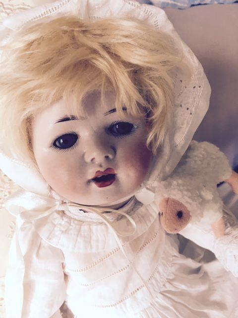 Een hele aparte baby pop van Theodor Wendt. Ze heeft een realistisch gezichtje met blauwe slaapogen en kuiltjes in de wangen. Haar pruik was vergaan, daarvoor in de plaats deze mooie volle mohair pruik. Ze draagt een antieke doopjurk met bijpassend mutsje. Er onder een katoenen luier, deze sluit met een heel oude veiligheidsspeld.   Bij de kop-rand zit aan de voorkant een streepje en er zit ook een streepje aan de achterkant boven het cijfer 3. Ik denk dat ze hier mee geboren is want het…