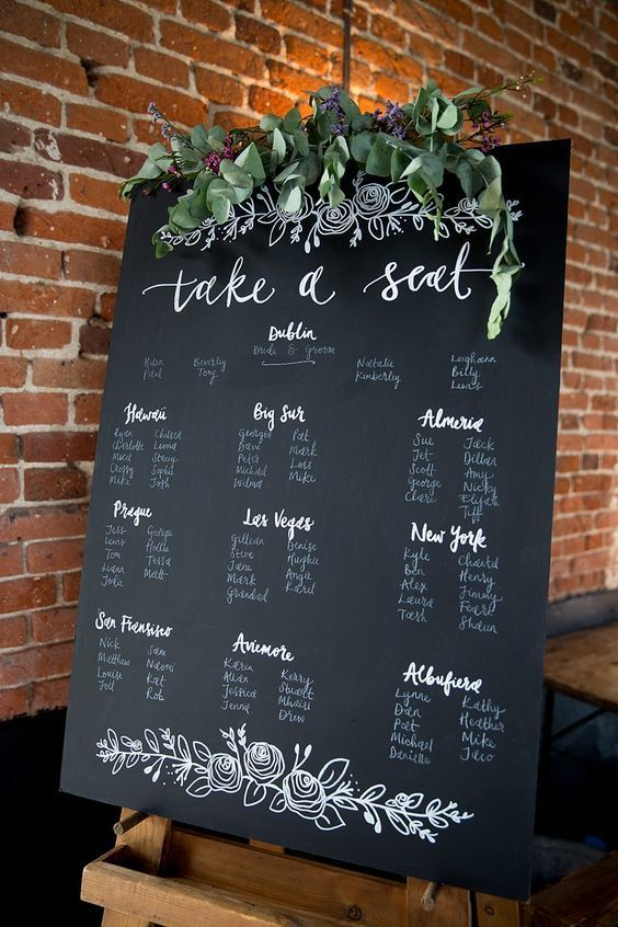 DIY Wedding Ideas for Brides Who Love Lettering | Since the seating chart is one of the first things your wedding guests will notice when they arrive to your reception, make sure it's amazing. This bride wrote each name on a black poster board and set it upon a wooden easel. The white calligraphy really pops against the dark background and green accent pieces.