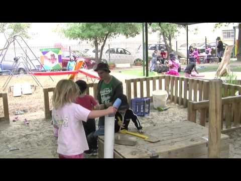 Vignette No. 16: 'Sandpit play'...This vignette shows an educator engaging with and supervising groups of children of mixed ages, three to five year olds, playing in the sandpit with implements. An outdoor activity designed and organised to engage every child in experiencing both built and natural environments.