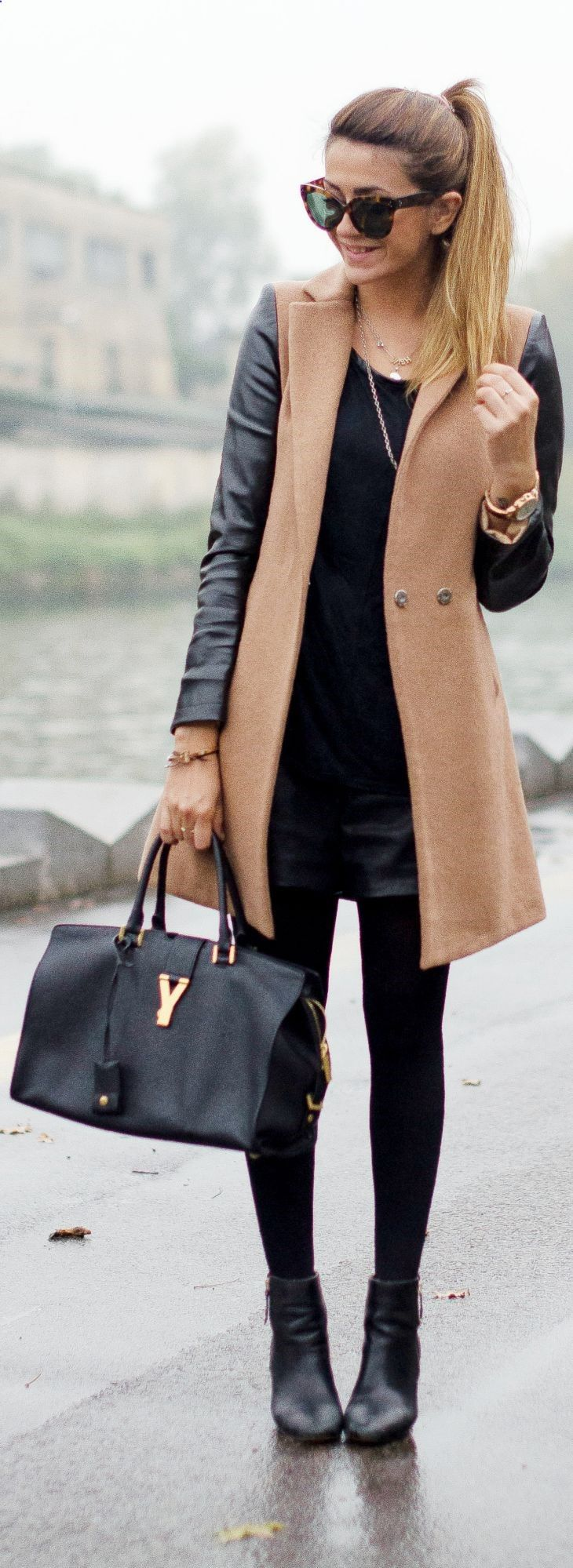 Two toned jacket with camel body and black leather sleeves, black leather booties and shorts with black tights and top.