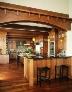 Das Foto zeigt eine Idee für elegante Holz unter dem Motto Küche mit einem Bogen über der Küchenbar. Es hat auch Shaker-Schränke, mittlerer Ton Holz Schränke, graue Backsplash und Edelstahlgeräte. Verschiedene Dekorationen sind auch einschließlich der Blumenvase auf dem Tisch. In der Bar gibt es auch schwarze Stühle. Foto von B & B Custom Bauherren mehr traditionelle Küche Fotos