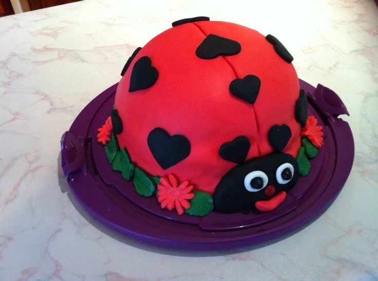 My attempt at a ladybug birthday cake topped with fondant for my daughter's 4th birthday party. :)  The bottom layer was your basic round cake tin but the top layer was baked in a round pyrex bowl that was approximately the right size to fit over the bottom layer. The decorations were cutouts using a fondant decorating kit I purchased cheap off ebay and the rest was just pure experimentation and absolute cuteness. :)