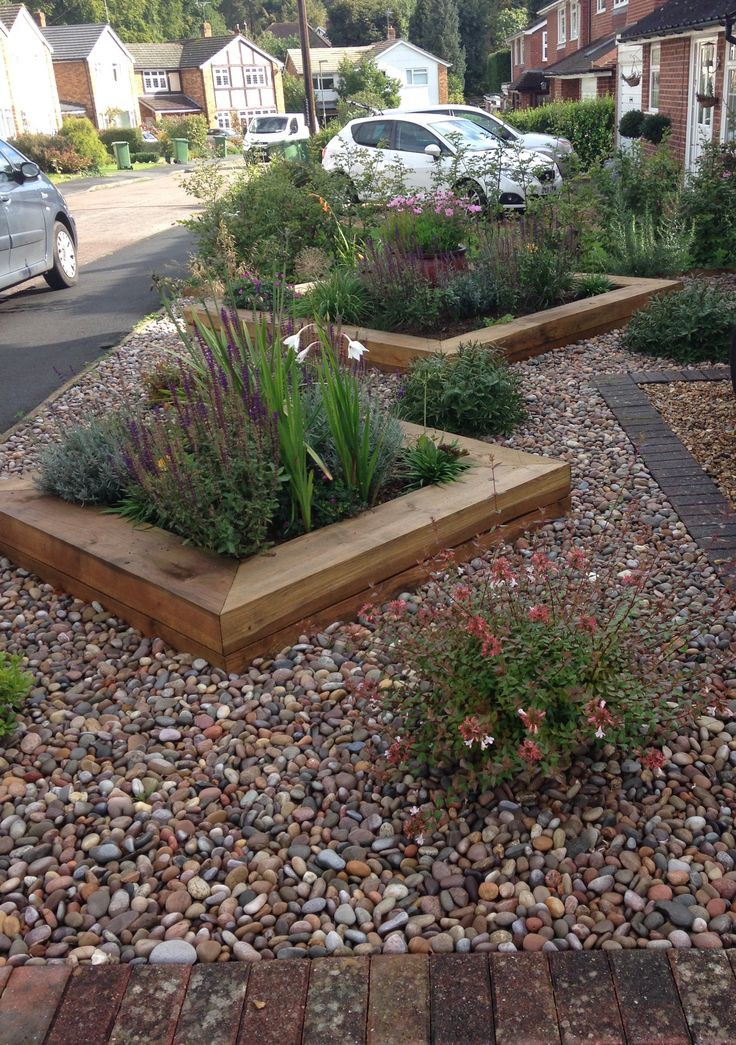 Raised borders in a front garden create controlled planting.  Low maintenance but plenty of interest