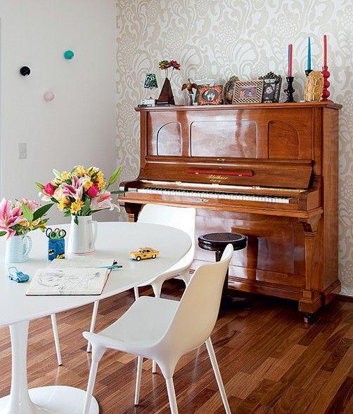 O piano é herança de família e fica na sala de jantar, na parede com destaque de papel estampado. A mesa Saarinen branca tem cadeiras na mesma cor. Projeto da arquiteta Claudia Pecego