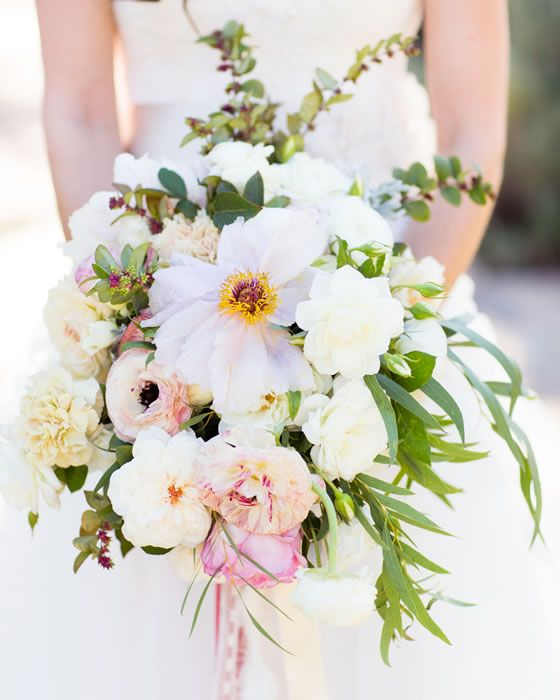 Poppies, roses, and ranunculus make up the bride's stunning bouquet. Wedding Planner: All You Need Is Love Events. Wedding Photographer: Johnathan Young Weddings.