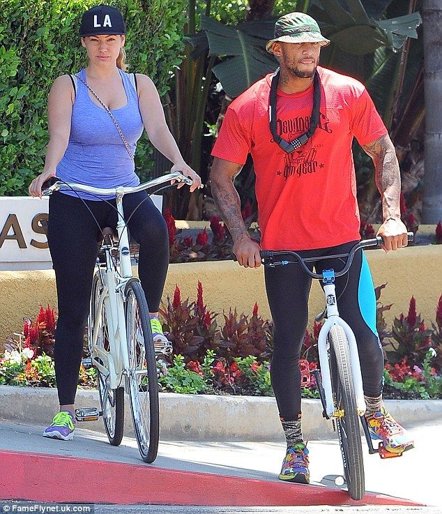Get a room! Kelly Brook and David McIntosh share a passionate kiss during bike ride around Los Angeles