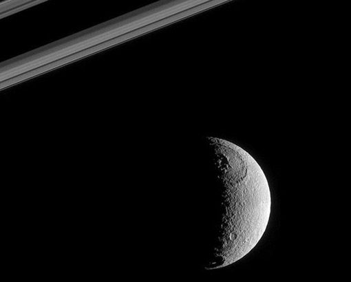 """Moons of Saturn : Tethys Discovery News This 665 mile wide moon of Saturn, , pronounced """"teeth-this,"""" has an ice-covered surface criss-crossed with cracks and faults. In this Cassini snapshot, a small mountain range inside the Odysseus crater can be seen. Covering about two-fifths of Tethys' surface, the crater is enormous, and the mountains are thought to have formed from shifting surface ice.  CREDIT: NASA/JPL/SPACE SCIENCE INSTITUTE"""