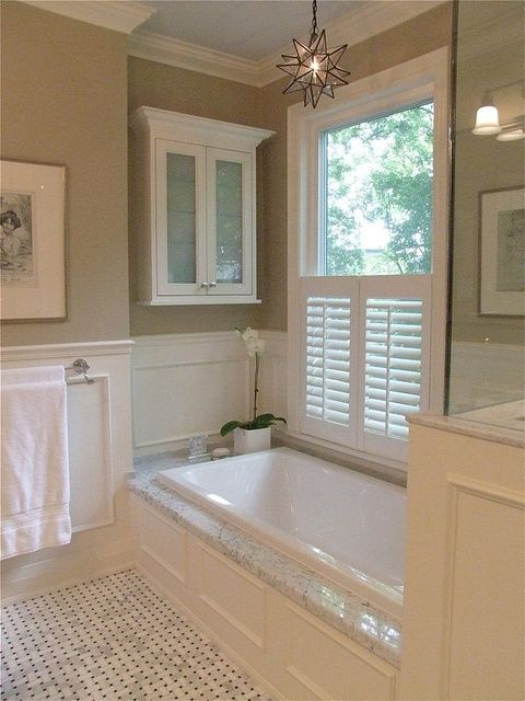 Chandelier Above Soaking Tub, Plantation Shutter at Base of Window, Khaki Paint with Trim Panels Below Chair-Rail Molding, Italian Marble Tile -Fabulous Owner's Bath!