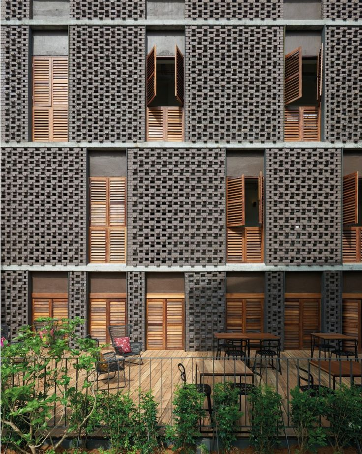 exterior, open cell dark brown brick and wood shutters | Lantern Hotel / ZLGdesign
