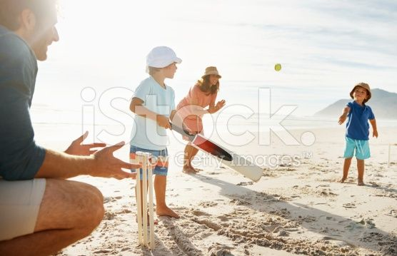 Family playing cricket at a beach in the sun royalty-free stock photo