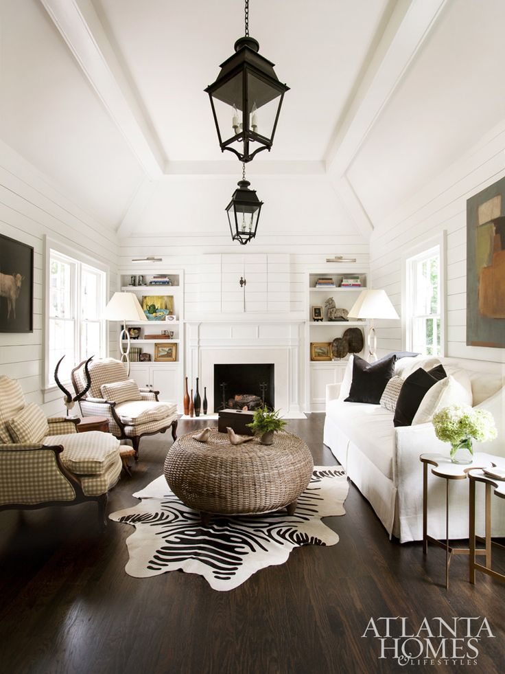 Shiplap siding and a vaulted ceiling highlight the cottage charm of the family room, which is adorned with rustic accents like a cowhide rug, a coffee table from Huff Harrington Home and vintage French lanterns.