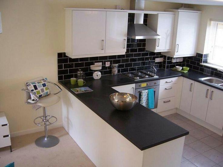 Paraschizzi nero e cucina bianca
