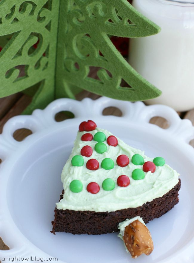 Easy Christmas Tree Brownie Treats! Bake brownies in a round pan, cut into wedges, top with green frosting and Mini M for lights and add a pretzel for the tree trunk!