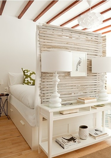 The Brooklyn Home Company designers demonstrate how to maximize a small space in a studio apartment. Here the bed is wrapped on 2 sides with wood lathe to divide the space, provide privacy, & add a unique aesthetic / http://www.thebrooklynhomecompany.com/portfolio/15th-street-3a4a/