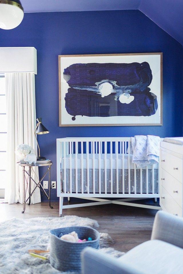 Baby Blues Nursery via MyDomaine. White modern crib, large scale blue abstract art, white changing table, hicks light pendant, sheepskin rug.