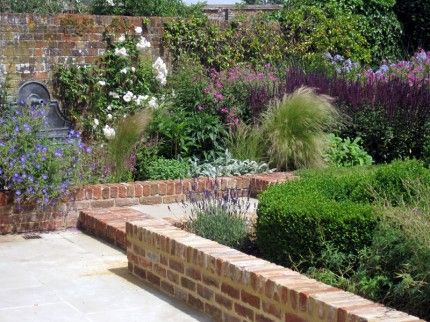 brick garden walls, perennial border, bronze fountain