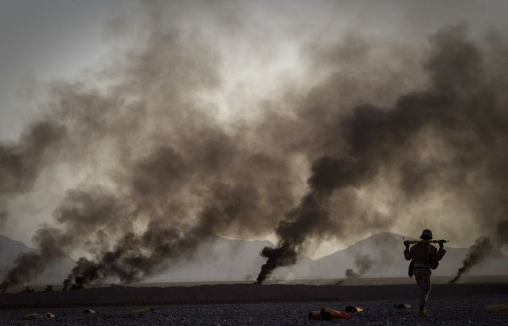 A US Marine on his way to pick up food supplies after they were dropped off by small parachutes from a plane outside Forward Operating Base Edi in the Helmand Province of southern Afghanistan, Thursday, June 9, 2011. The smoke in the background comes from burning parachutes the Marines destroy after they reached the ground.