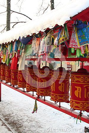 Red prayer wheels and prayer flags - lungta under snow-covered visor in the courtyard of the Datsan Gunzechoinei. St. Petersburg, Russia