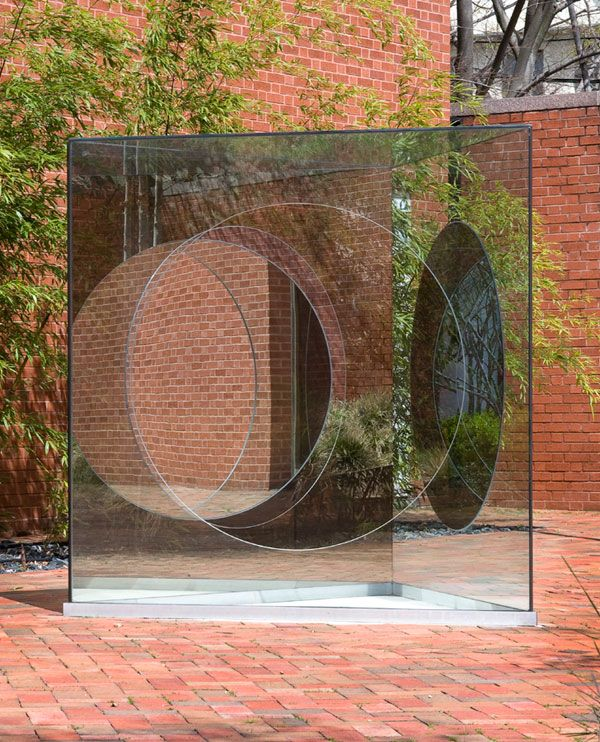 Dan Graham: Triangular Solid with Circular Inserts, 1989. Two-way mirror, clear glass and aluminum, 72 x 72 x 72 in. Weatherspoon Art Museum University of North Carolina, Greensboro.