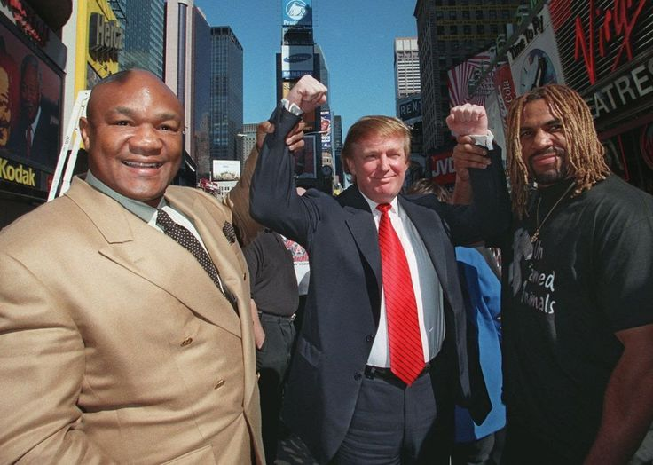 Boxers George Foreman, left, and Shannon Briggs, hold up the arms of Donald Trump during a news conference at the Official All Star Cafe in New York Tuesday Oct. 21, 1997. Foreman and Briggs will be fighting for the heavyweight crown next month at Trump Taj Mahal in Atlantic City. (AP Photo/Albert Ferriera)