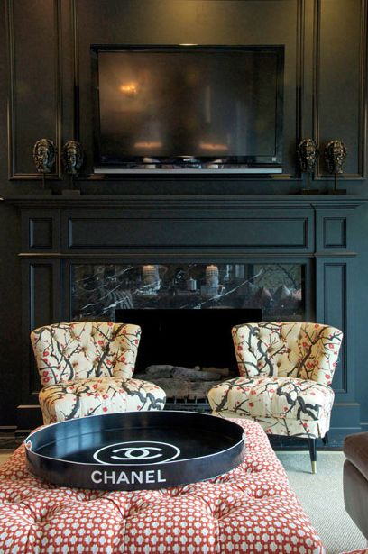 living rooms - Braemore Flowering Branch Silk tufted chair black caster legs black walls black fireplace polished black marble pink geometric pattern fabric tufted ottoman round black Chanel tray