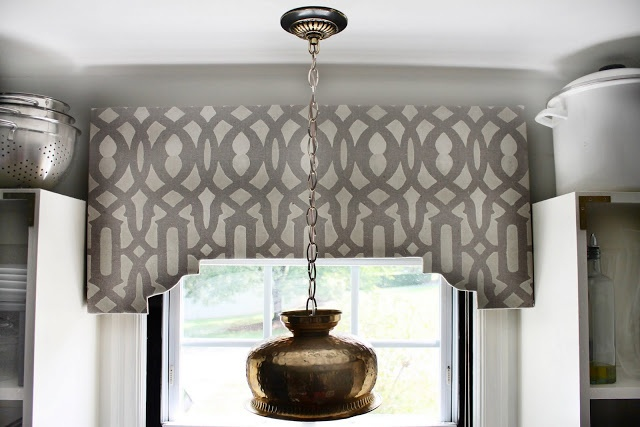 I never get tired of shaped cornices .. this is great at this kitchen sink window and love the light fixture - DIY Stenciled Cornice Board