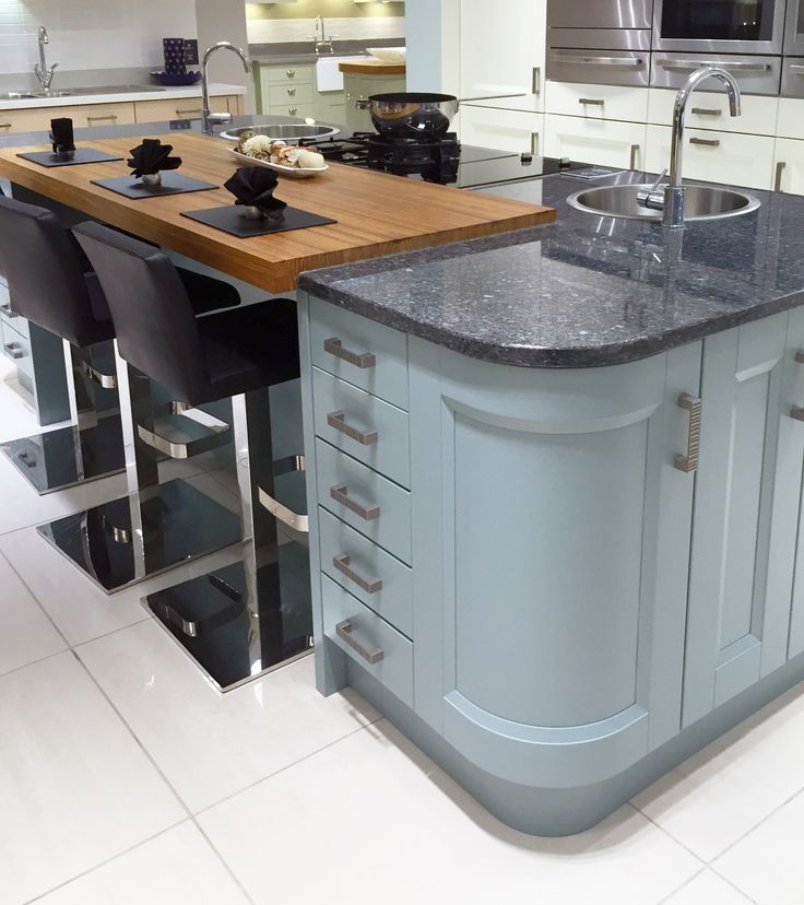 Contemporary kitchen island design in blue, with curved units, inset wooden breakfast bar and granite worktops. www.sheratonkitchens.co.uk