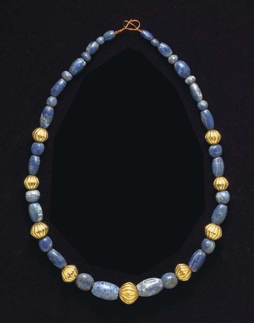 A WESTERN ASIATIC GOLD AND LAPIS LAZULI BEAD NECKLACE   CIRCA 3RD-2ND MILLENNIUM B.C.   Composed of thirty-four lapis lazuli spherical and barrel-shaped beads, slightly graduated in size, interspersed with nine gold biconical fluted beads; strung on a modern wire with looped ends  27 in. (68.6 cm.) long