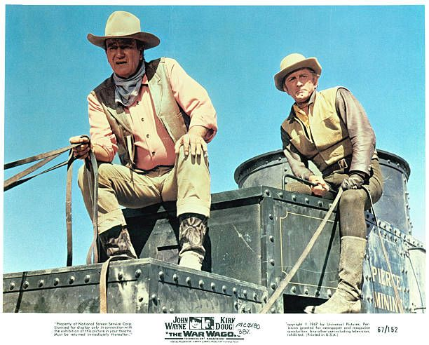 John Wayne and Kirk Douglas holding the reins of their captured armored stagecoach in a scene from the film 'The War Wagon' 1967