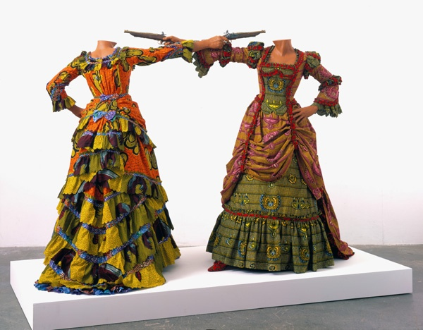 Yinka Shonibare, How to Blow up Two Heads (Ladies), 2006. Two fiberglass mannequins, two prop guns, Dutch wax printed cotton textile, shoes, leather riding boots, plinth. Museum purchase with funds provided by Wellesley College Friends of Art, 2007.124.1-.2  Read / lire : https://www.davismuseum.wellesley.edu/whats-on/past/sculpture-from-the-davis-collections