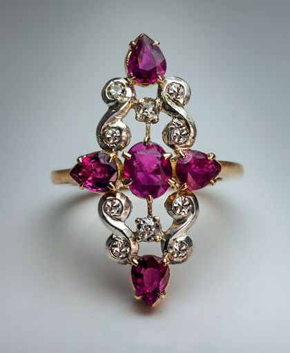 A Vintage Art Deco Ruby and Diamond Ring 1920s S-scroll motif platinum topped 14K gold openwork ring set with fine rubies, single cut and old mine cut diam