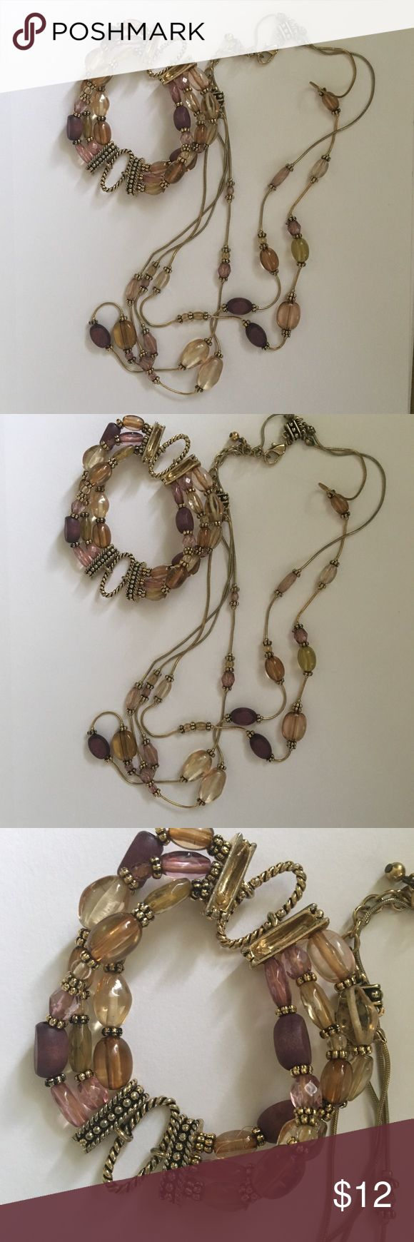 Necklace and bracelet set Necklace and bracelet set.  Necklace has lobster clasp and bracelet has three rows of elastic covered in beads and gold.  Colors are slight green,smoky topaz, lavender, and dark purple. Jewelry Necklaces