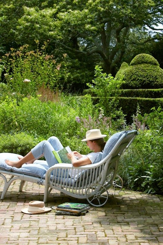 Tara Dillard: evergreen clipped hedges, perennial border, brick terrace, lounge chair, trees, sky