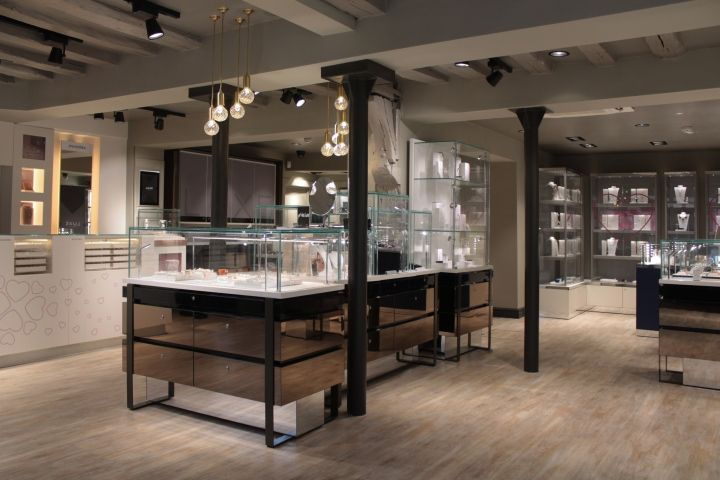 Throughout the store, soft warm grey tones are complemented by burnished bronze details and a light oak floor. Smoked mirrored cabinets and leather furnishings add to the overall sense of luxury.