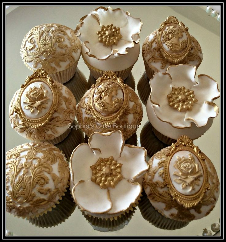 Rococo Cupcakes - A collection of elaborate Rococo inspired gold and ivory fondant wedding cupcakes with edible sugar brooches & flowers hand painted with gold lustre finished with genuine victorian antique lace. They accompanied a two tier wedding cake in a cupcake tower.